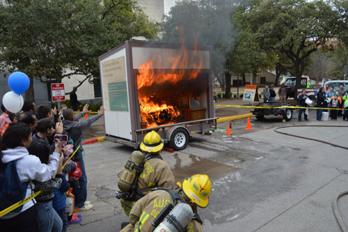 students observing an FPS live fire demonstration, fire fighters putting out the blaze in contained trailer